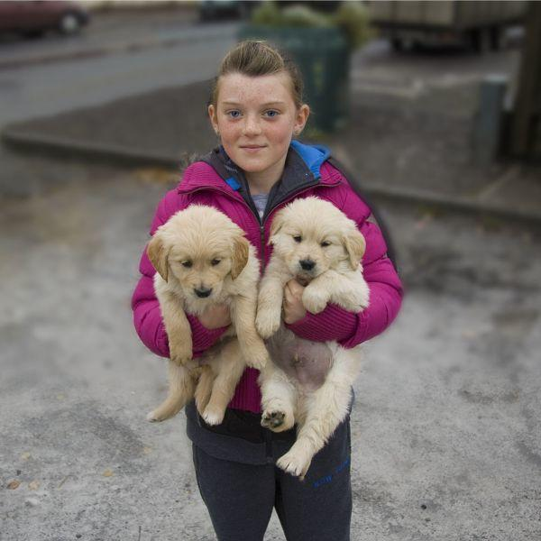 photograph of girl holding two puppies