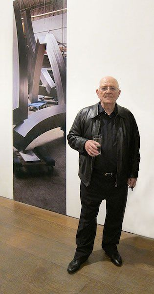 """Brian Wall at his """"New Works"""" exhibition Flowers Gallery, London in front of mural produced by Blow Up Lab"""