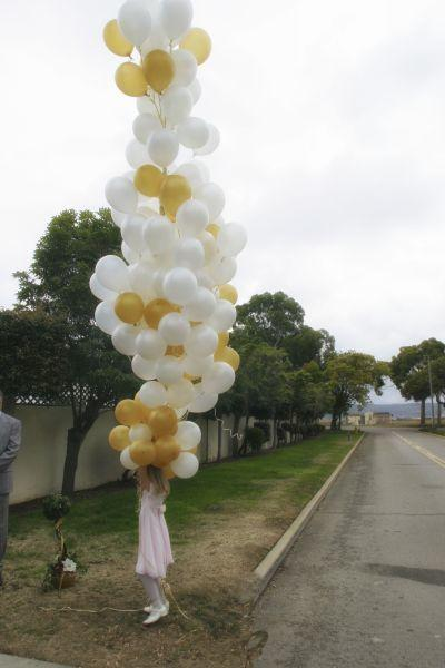 Snapshot of festively dressed girl holding a bunch of white and golden balloons