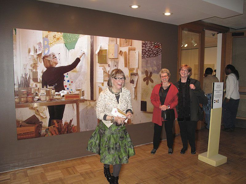 Squeak Carnwath in front of a photographic print of her painting